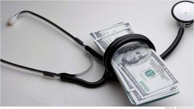 Stethoscope wrapped around hundred dollar bills